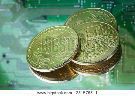 Three Golden Bitcoins With Reflections On Printed Circuit Board Background