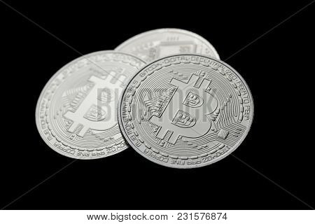 Three Platinum Silver Colored Bitcoins On Black Background