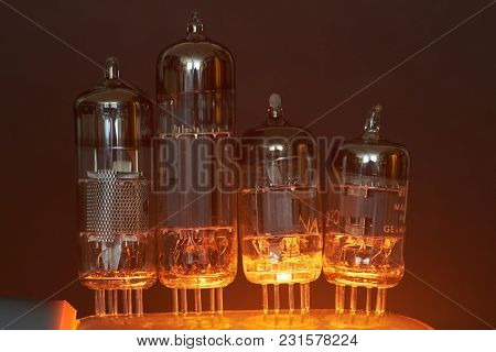 Four Old Electron Tubes Are Illuminated From Below.