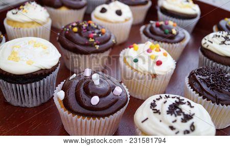 Chocolate And Vanilla Cupcakes Close-up. Homemade Decorated Chocolate And Vanilla Cupcakes Closeup O