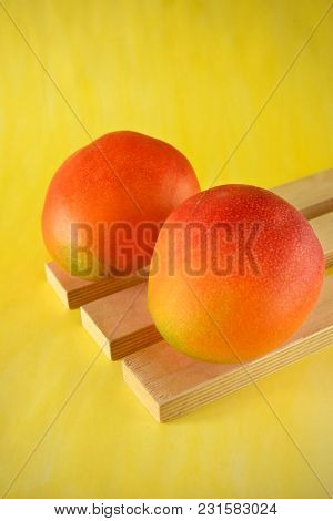 Two Ripe Mangoes On Wooden Boards On Bright Yellow Background