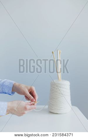 Female Hands With Knitting, On White Table Vase Spool Of Wool With Needles, On A Blue Background