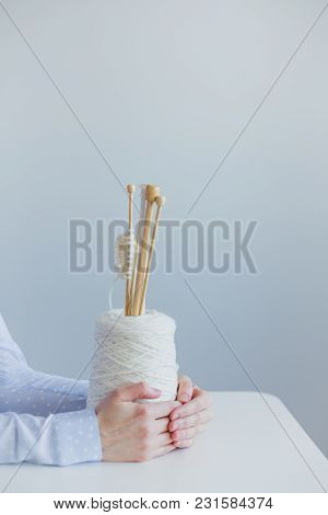 Female Hands On A White Table Holding A Spool Of Wool With Knitting Needles, Blue Background
