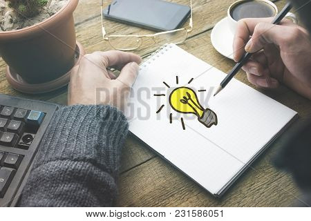 Idea-light Bulb On Notepad With Man Hand Pen On Working Table