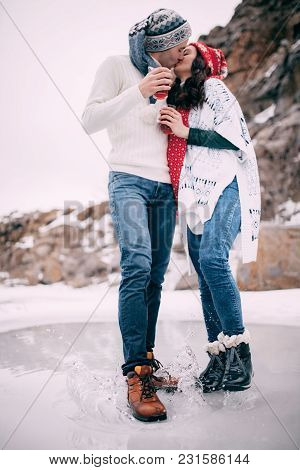 Young Couple With Cups Of Hot Tea In Their Hands Is Kisssing And Standing In Puddle Of Melted Water