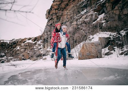 Young Man Carries His Girlfriend On Back Across Puddle Of Melted Water With Flying Apart Water Splas