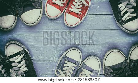 Six Pairs Of Old, Worn Sneakers On A Lilac Wooden Surface, Top View, Vintage Toning