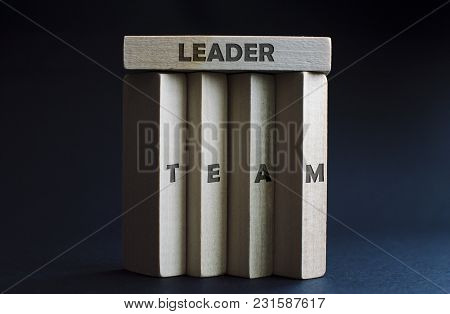 One Wood Block As A Team Leader Teaming Up Four Vertical Wood Blocks As A Team. Concept Of Business,