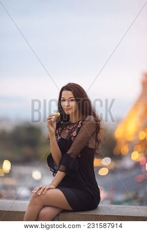 Paris Woman Smiling Eating The French Pastry Macaron In Paris. Evening Eiffel Tower With Lights In T