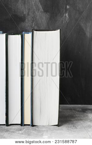 Pile Of Various Books On Dark Background. Copy Space
