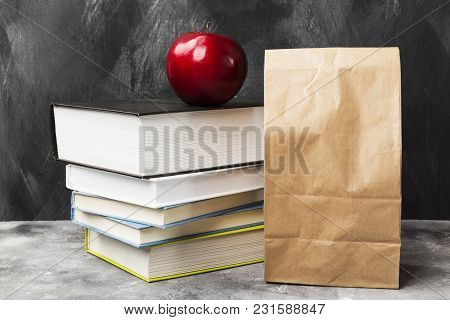 Pile Of Various Books, Red Apple And Package Of Lunch On Dark Background
