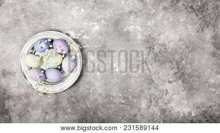 Multicolored Eggs For Easter In Marble Plate With White Flowers On Gray Background. Top View, Copy S