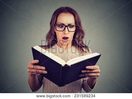Young Shocked Girl In Glasses Stunned With Information In Book Standing On Gray.