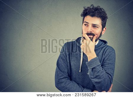 Casual Bearded Man Touching Chin And Looking Away In Doubts Making Choice.