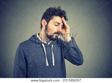 Young Casual Hipster With Beard Suffering From Misfortune Looking Tired While Rubbing Head.