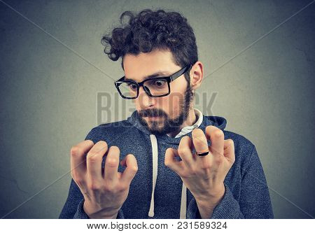 Young Serious Man With Obsessive Compulsive Disorder Exploring Cleanliness Of Hands.