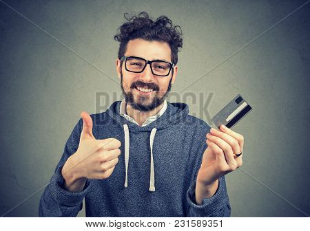Happy Man Holding A Credit Card Showing Thumbs Up