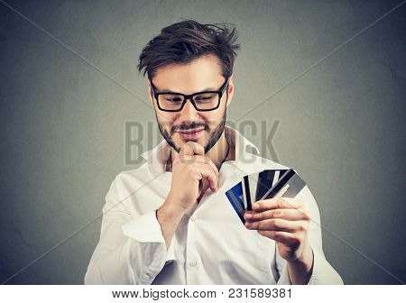 Young Handsome Man In Glasses Having Choice Of Credit Cards Excited With Financial Stability.