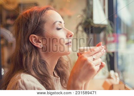 Side View Of Content Woman Smelling Aroma Of Freshly Made Coffee Holding Cup With Eyes Closed.