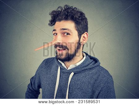 Liar Man With Long Nose Isolated On Gray Background. Human Emotions, Feelings.