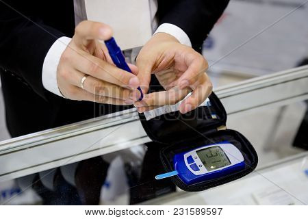 Man Pricking A Finger For Measuring Glucose Level In His Blood Drop By Using Digital Glucometer.
