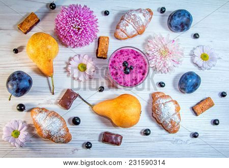 Ripe Fruits - Pears And Plums, Berry Smoothie, Flowers, Croissants And Chocolate Candies On A Wooden