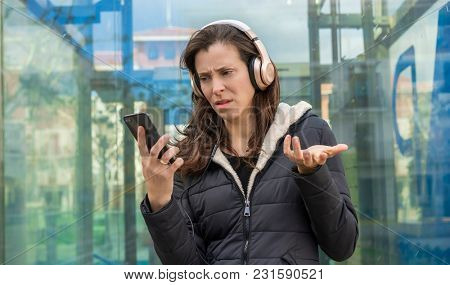 Relation, jealousy and suspicion in the cell phone, couple problems, adult woman looking at suspicious messages on the phone while on the street listening to music with headphones
