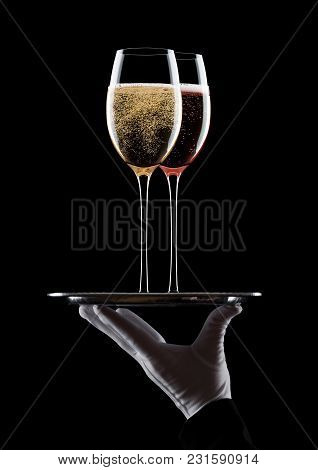 Hand With Glove Holds Tray With Yellow And Pink Champagne Glasses With Bubbles On Black Background