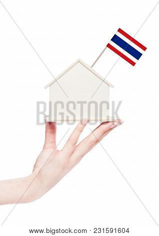 Female Hand Holding Wooden House Model With Thailand Flag On Top