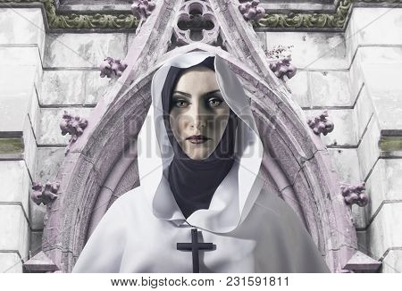 A Beautiful Nun In White Hooded Cloak With Cross On Her Neck Standing On Temple Background.