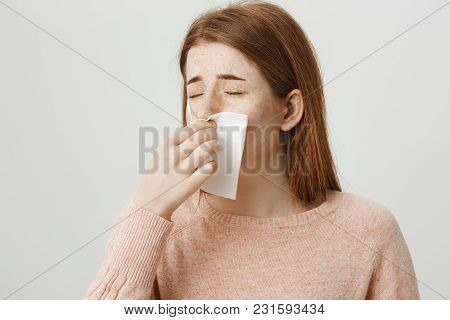 Close-up Portrait Of Upset Redhead Girl Having Cold Or Flu, Blowing Nose In Napkin While Frowning An