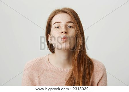 Close-up Portrait Of Sensual Attractive Redhead Woman With Freckles Folding Lips As If Wanting To Ki