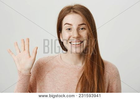 Close-up Portrait Of Cute Ginger Girl Waving With Hand And Smiling Broadly At Camera While Standing