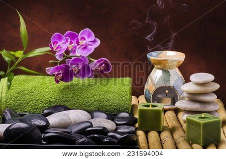 Wellness Environment With Orchid, Massage Stones And Aromatherapy With Candles And Essential Oils