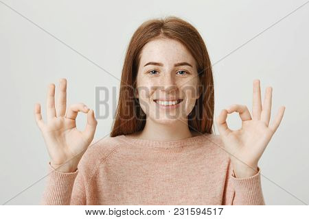 Close-up Studio Portrait Of Smiling Positive Redhead Woman Showing Okay Or Great Gestures With Both