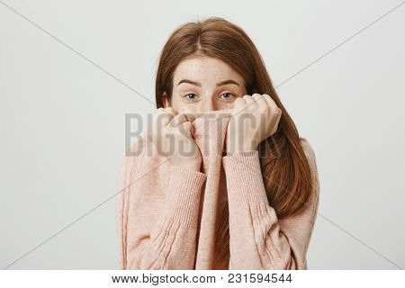 Studio Portrait Of Cute Redhead Caucasian Student Covering Half Face With Pullover, Looking Out Of C
