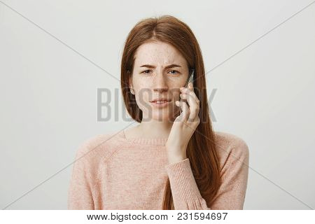 Close-up Portrait Of Cute Caucasian Redhead Girl Talking On Smartphone And Expressing Disbelief, Sus