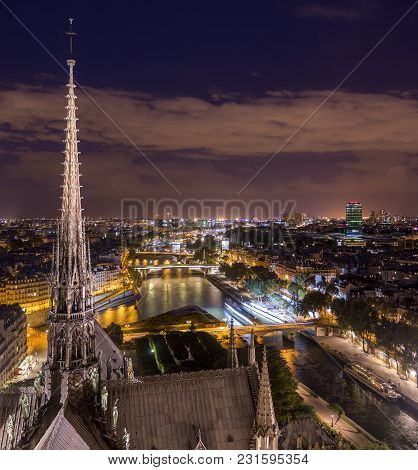 View Of Illuminated Old City From Viewpoint Of Old Gothic Notre-dame Cathedral With Beautiful Spire