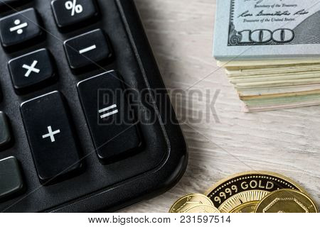 A Pile Of Gold Coins, Dollar Bills And A Calculator.