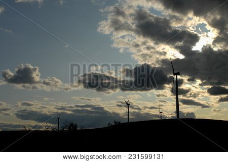 The Silhouette Of Several Massive Wind Turbines On A Hill With A Dark Cloudy Sky In The Background.