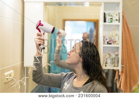 Happy Young Woman Blow Drying Hair In Bathroom.