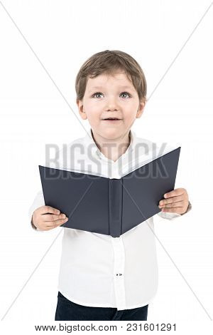 Portrait Of A Cute Little Boy In A White Shirt Holding An Open Book And Looking Upwards. An Isolated