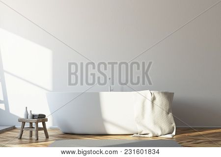 Interior Of A Modern Bathroom With White Walls, A White Bathtub Standing On A Wooden Floor And Shelv