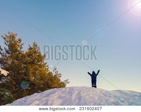 Boy Raises His Hands While Standing On Top Of Rocks. Winter. Snow Rocks
