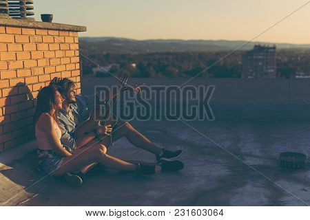 Couple In Love Hanging Out At A Rooftop Party, Sitting On The Floor, Leaning Against A Brick Wall An