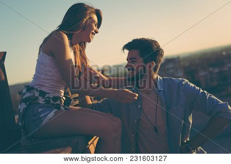 Couple In Love Having Fun On A Building Rooftop, Enjoying A Beautiful Summer Sunset Over The City