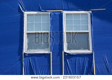 Hail Storm Damage Repair With Blue Cloth Covering Broken House Siding And Wooden Frame Made With Fur