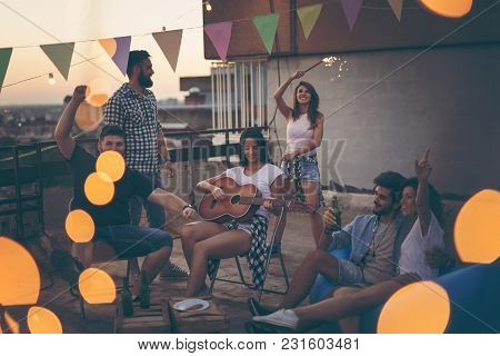 Young Friends Having Fun At A Summertime Rooftop Party, Playing The Guitar, Singing, Dancing And Chi