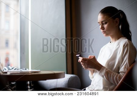Casual Dressed Hipster Girl Chatting In Social Network Via Mobile Phone While Sitting With Laptop Co