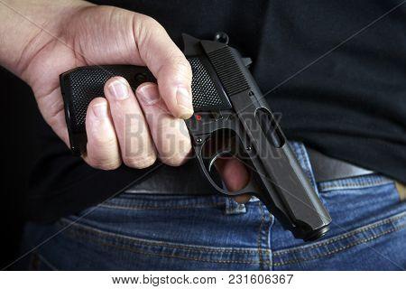 Hidden Gun In Hands Back Side To Man In Blue Jeans